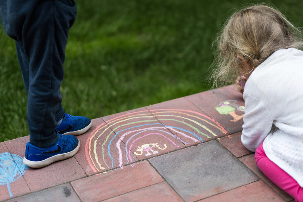 A little girl draws a chalk rainbow on her front porch.