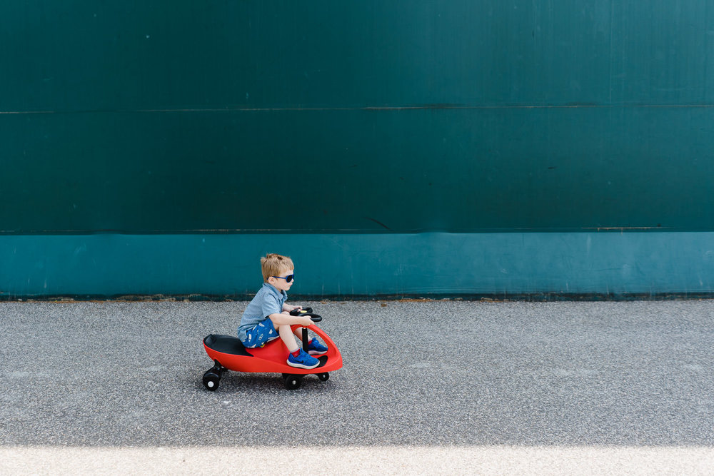 A little boy speeds by on a plasma car.