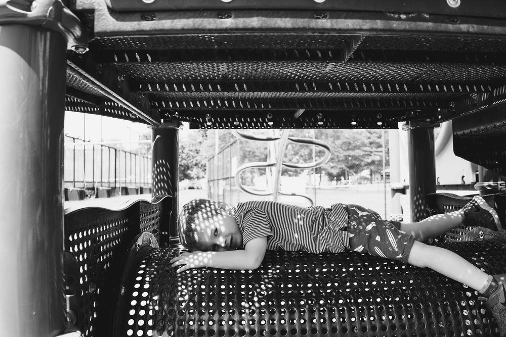 A little boy lies on a tunnel in a playground structure.