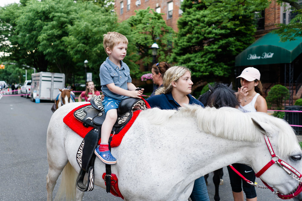 A little boy rides a pony at the Friday Night Promenade in Garden City.