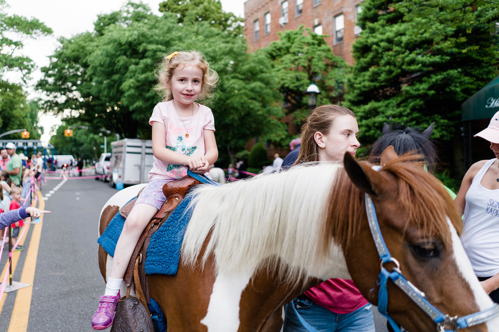A little girl rides a pony at the Friday Night Promenade in Garden City.
