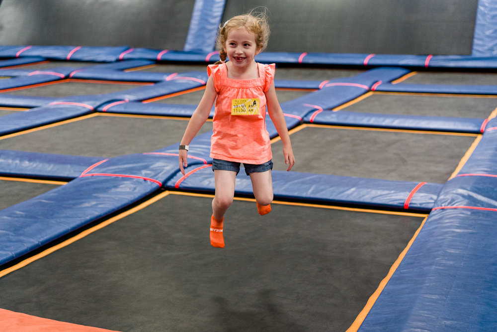 A little girl jumps on a trampoline.