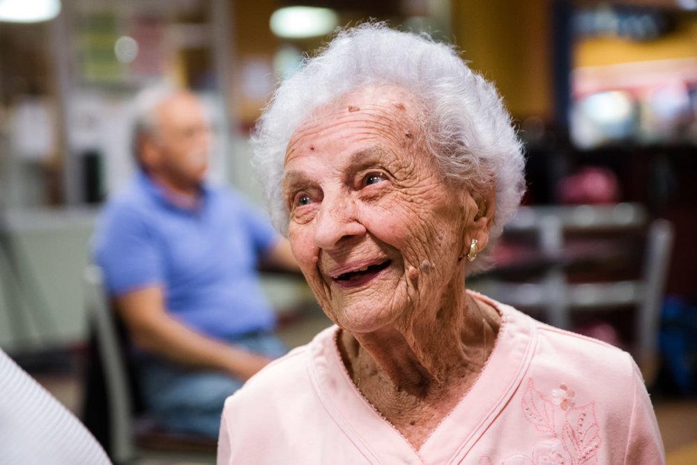 An elderly woman smiles.