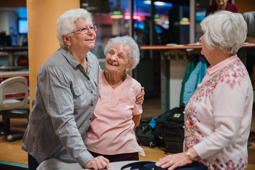 Senior women embrace at a bowling alley.