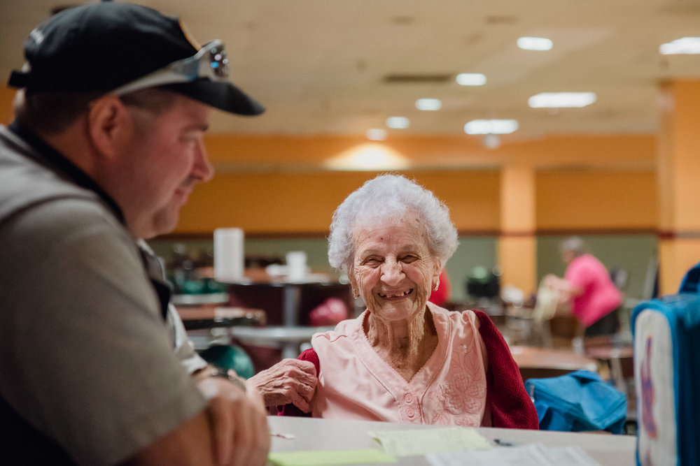 An elderly woman smiles at friends at a bowling alley.