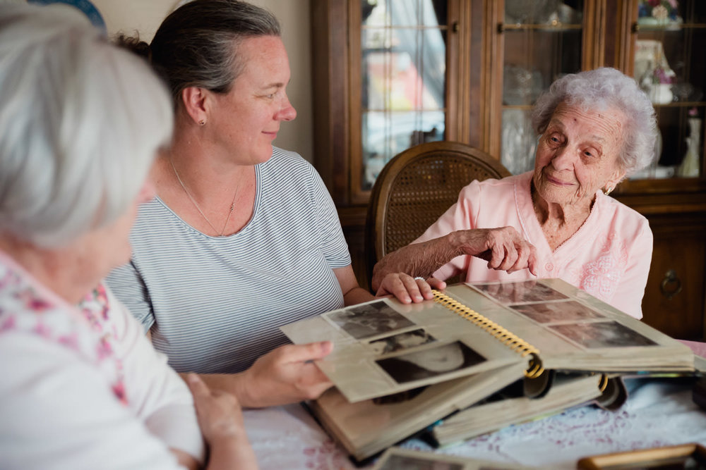 Three generations of women look through family photographs.
