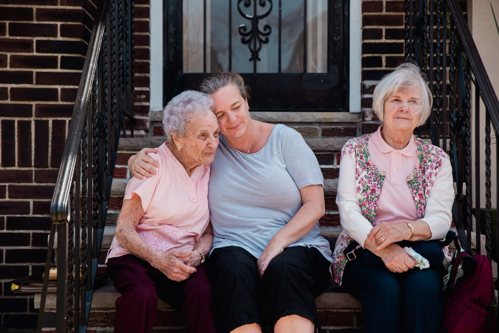 Three generations of women sit on a front stoop in Queens.
