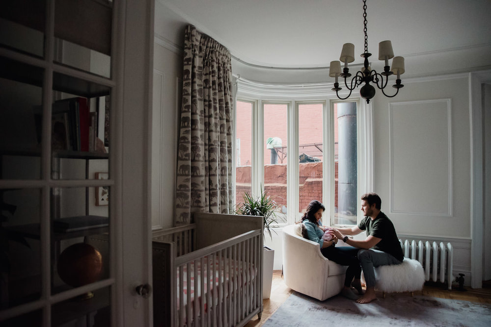 Parents sit in a nursery with their newborn baby.