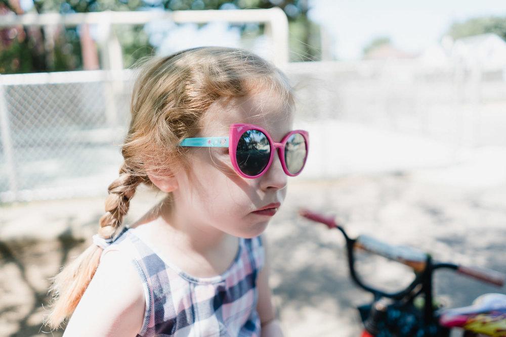A little girl wearing sunglasses.
