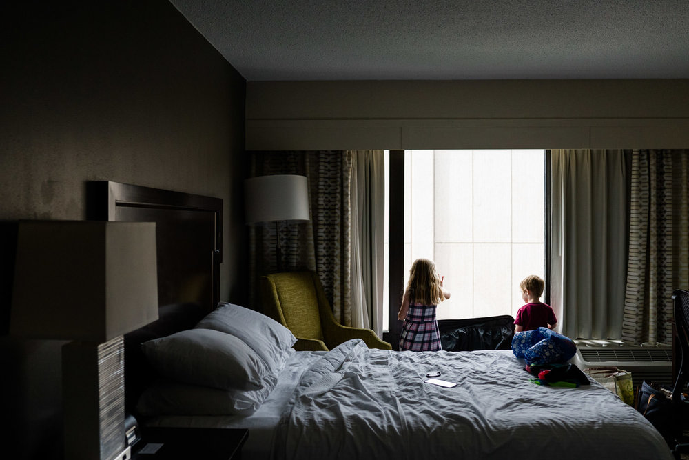 A little boy and girl look out a hotel room window.