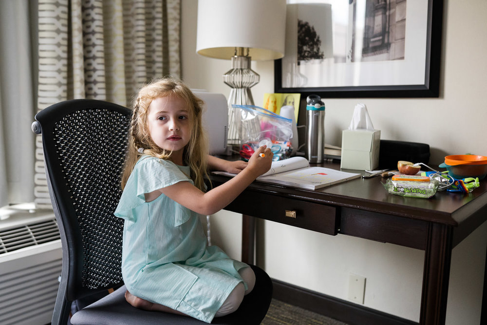 A little girl sits at a desk in a hotel room.