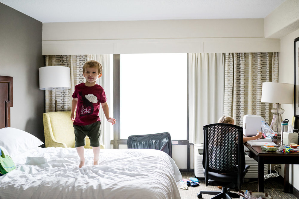 A little boy jumps on a hotel room bed.