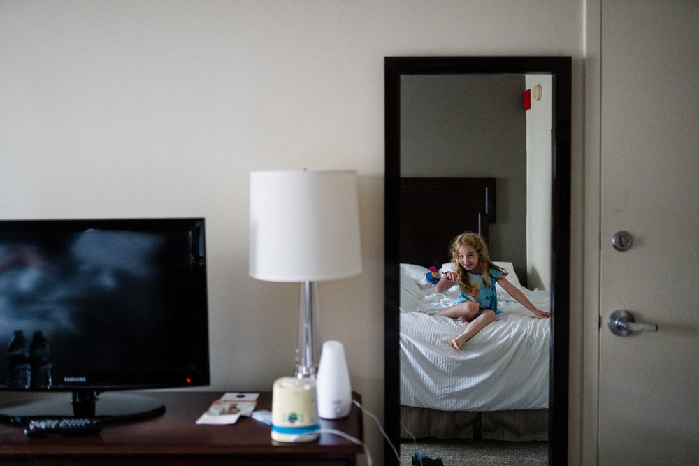 A reflection of a little girl in a hotel room mirror.