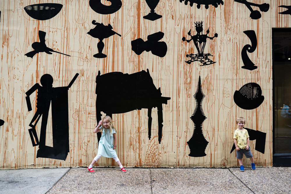 Children pose by a mural wall in Philadelphia.