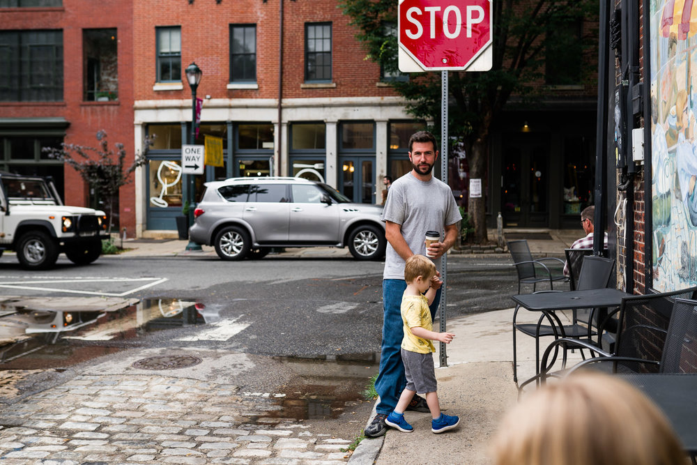 A father and son stand on a street corner in Philadelphia.