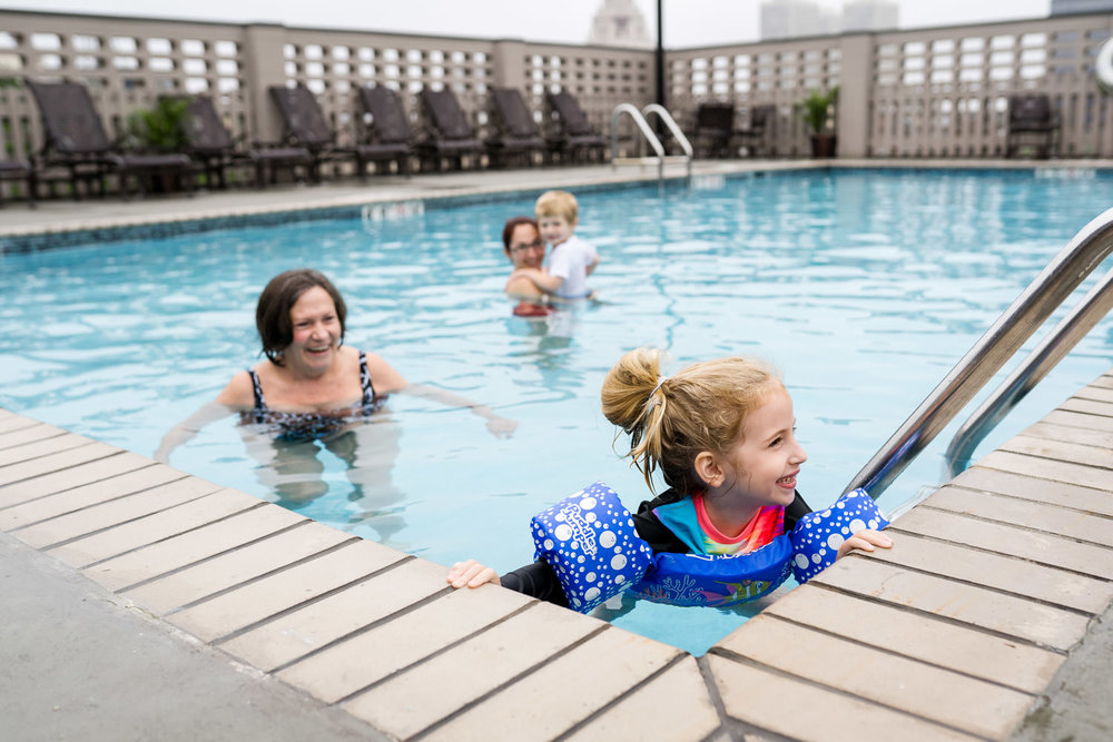Family members swim in a hotel pool.