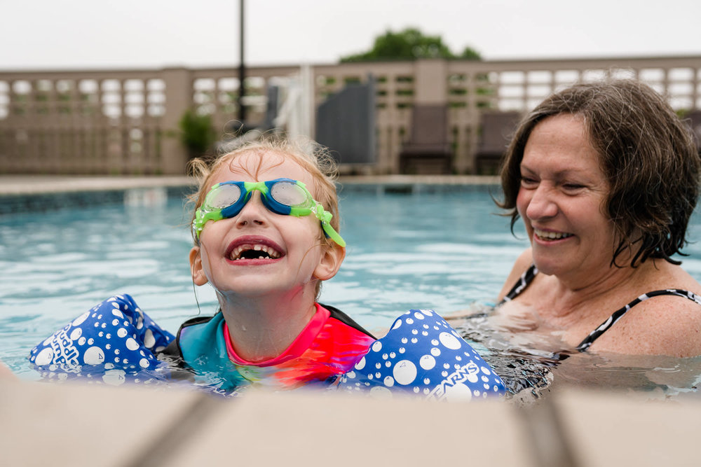 A little girl in swim goggles smiles to her grandmother.