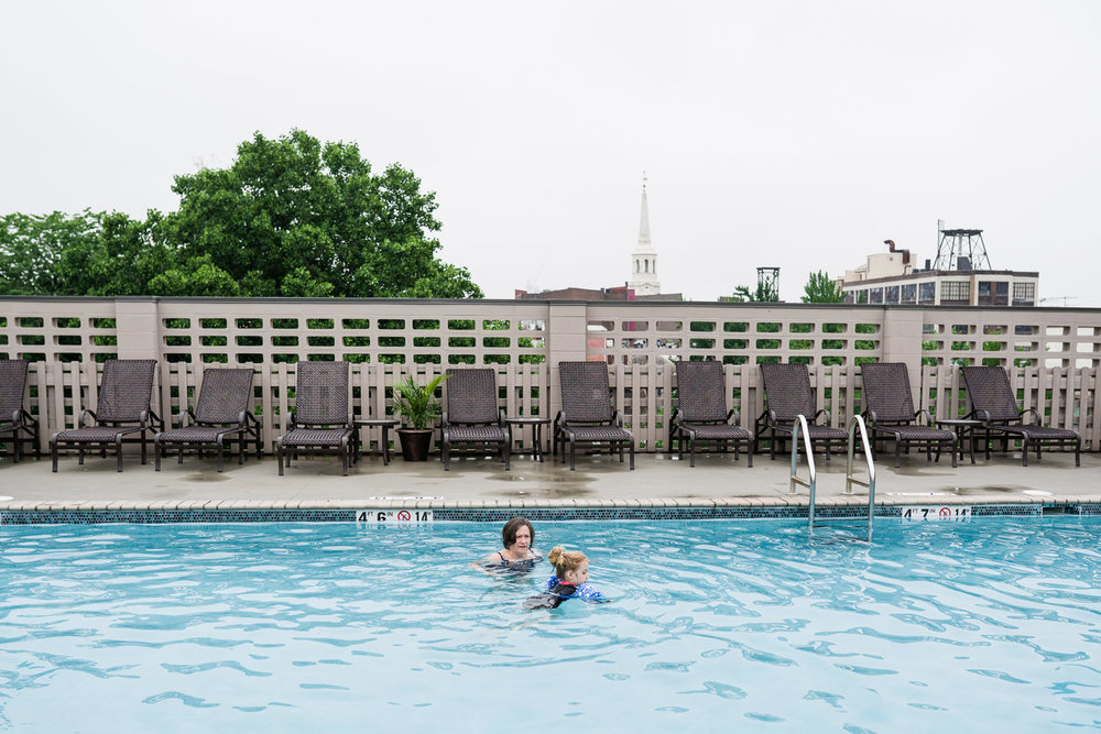 A little girl and her grandmother swim in a hotel pool.