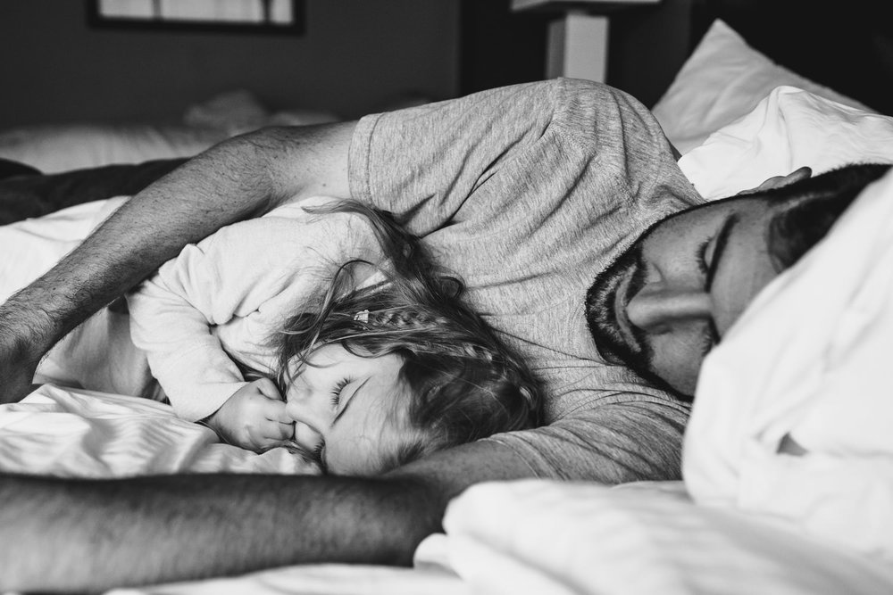 A father and young daughter cuddle on a bed.