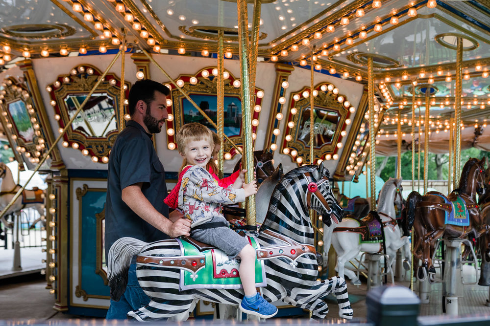 A boy rides a carousel.