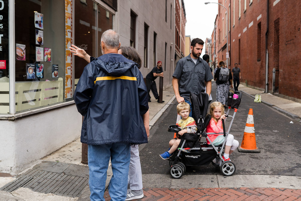 A father stands with his kids in a stroller on the street.