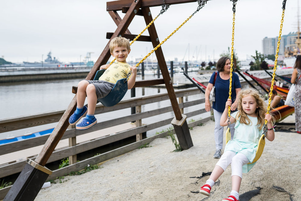 Children swing on a swingset at the pier.