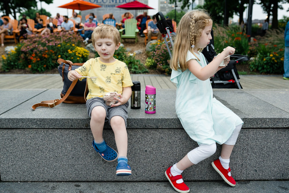 Children sit on steps and eat ice cream.