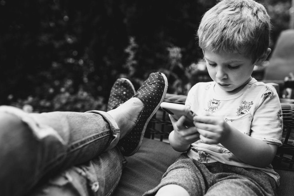 A little boy plays with a phone next to his mom.