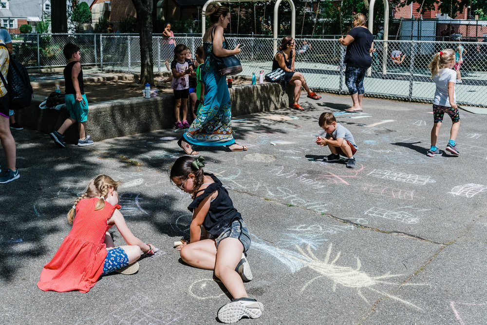Children draw with chalk at Garden City South playground.