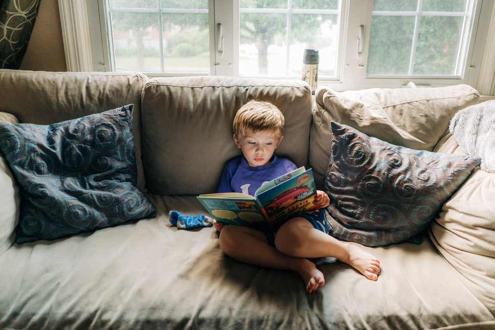 A little boy sits on the couch.