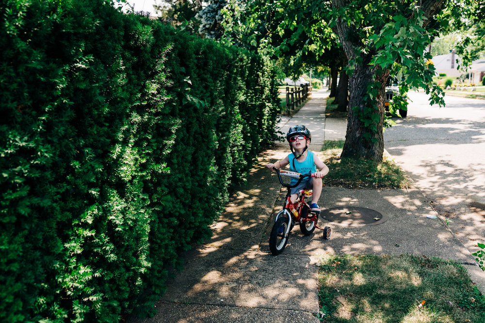 A little boy rides his bike through shadows of a tree.