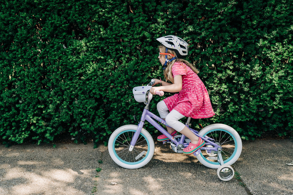 A little girl rides her bike.