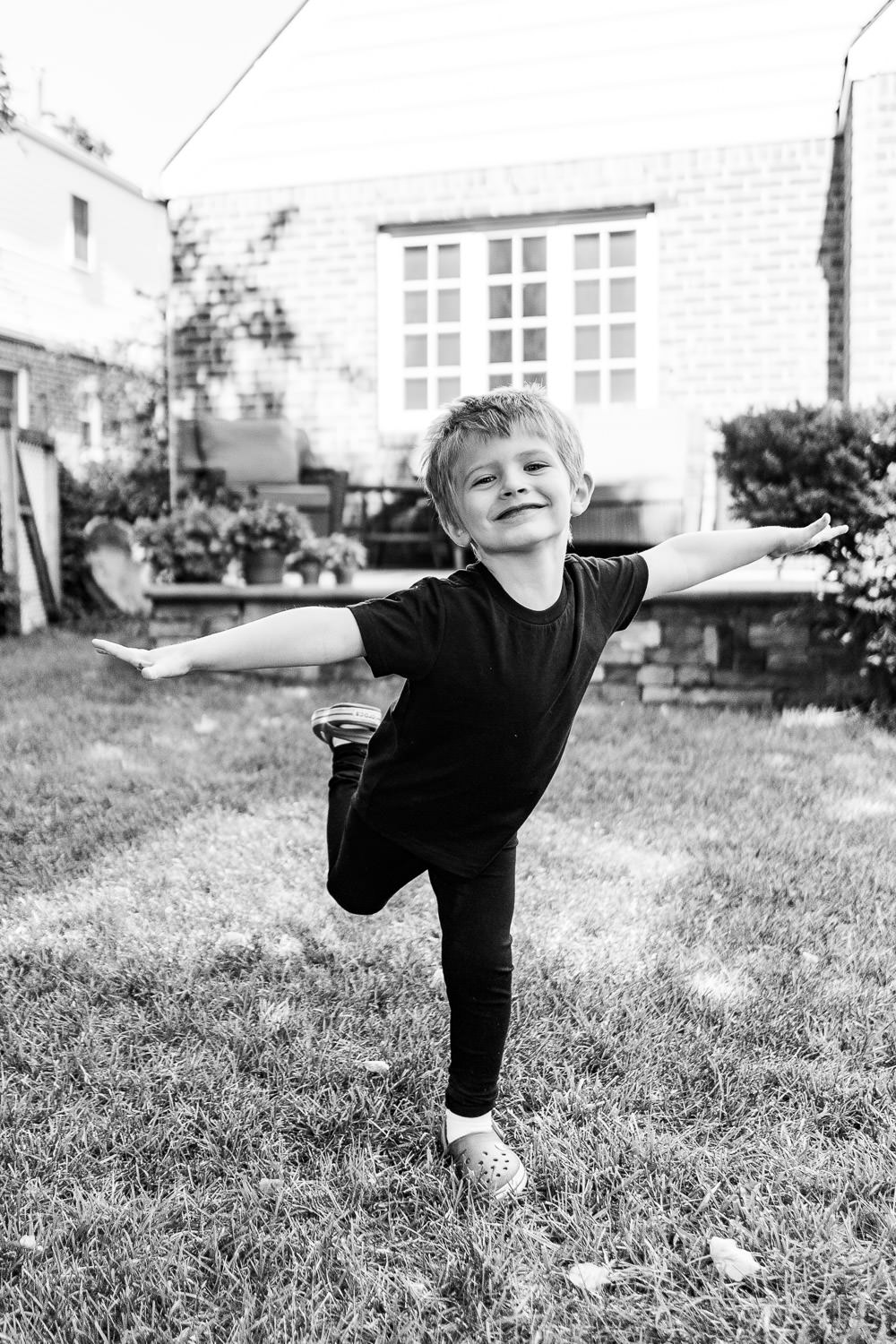 A little boy does ballet on his front lawn.