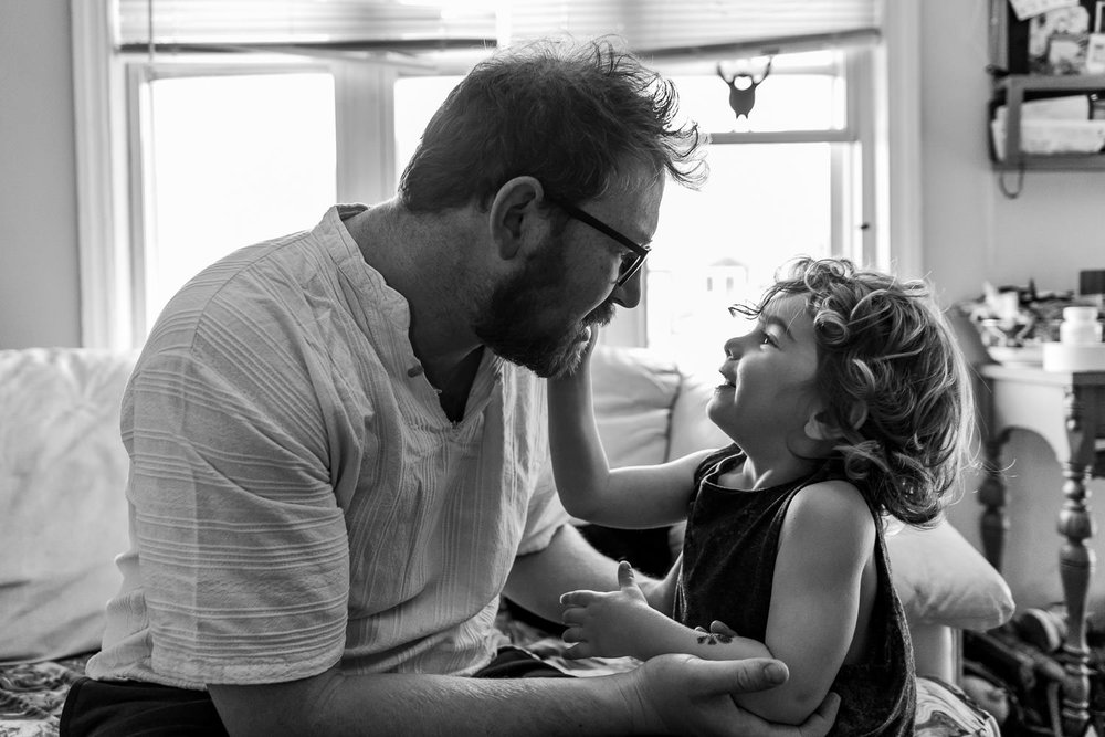 A little boy touches his father's face.