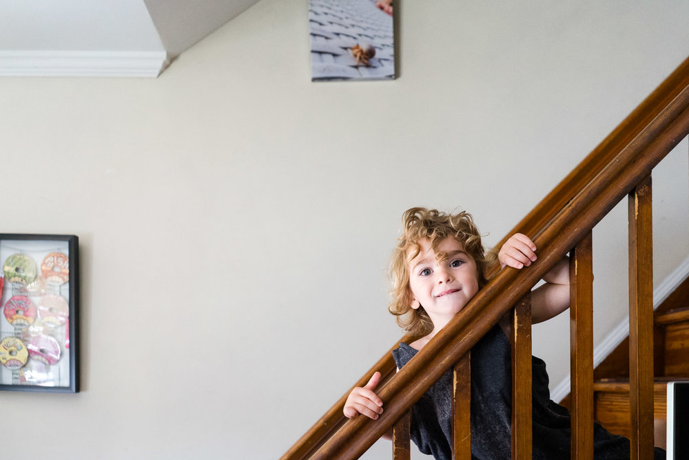 A little boy peers over the banister of the stairs.