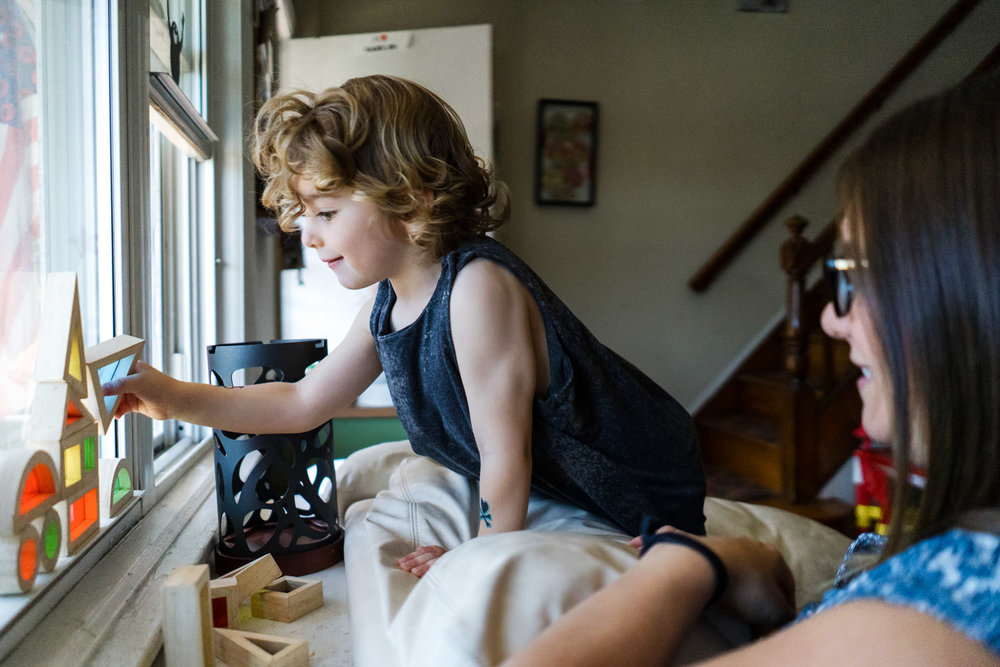 A little boy builds a structure on his window ledge.