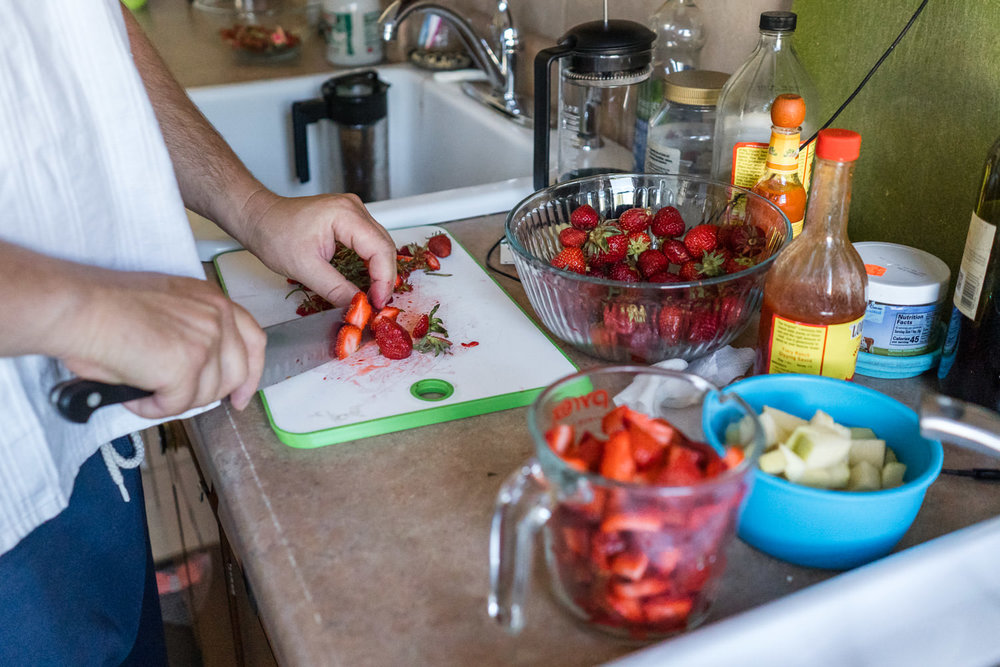 A man chops strawberries in the kitchen.