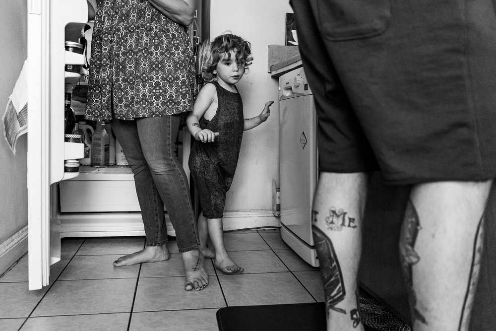 A little boy squeezes by his parents in the kitchen.