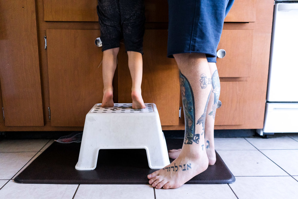 The feet of a father and son in the kitchen.