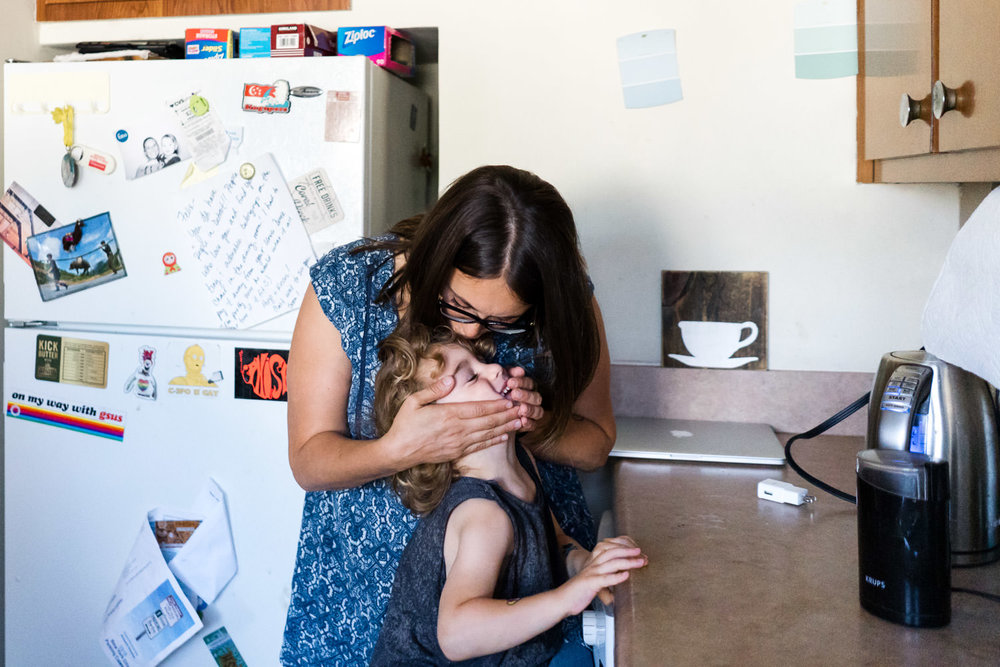 A mother kisses her son's head in the kitchen.