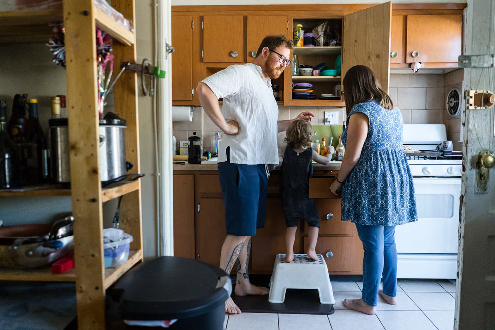 A family gathers around the kitchen sink.