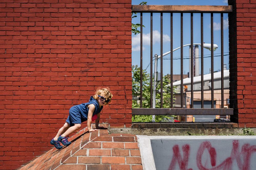 A little boy climbs a brick structure.