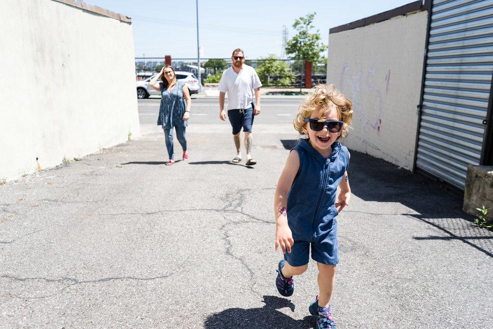 A little boy runs ahead of his parents.