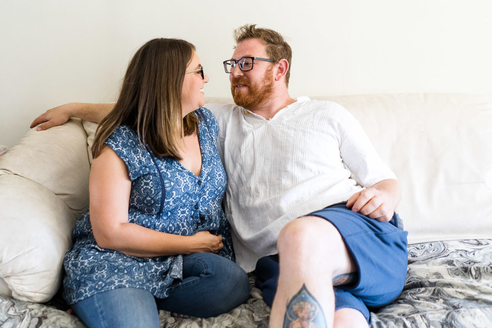 A husband and wife look at each other on the couch.