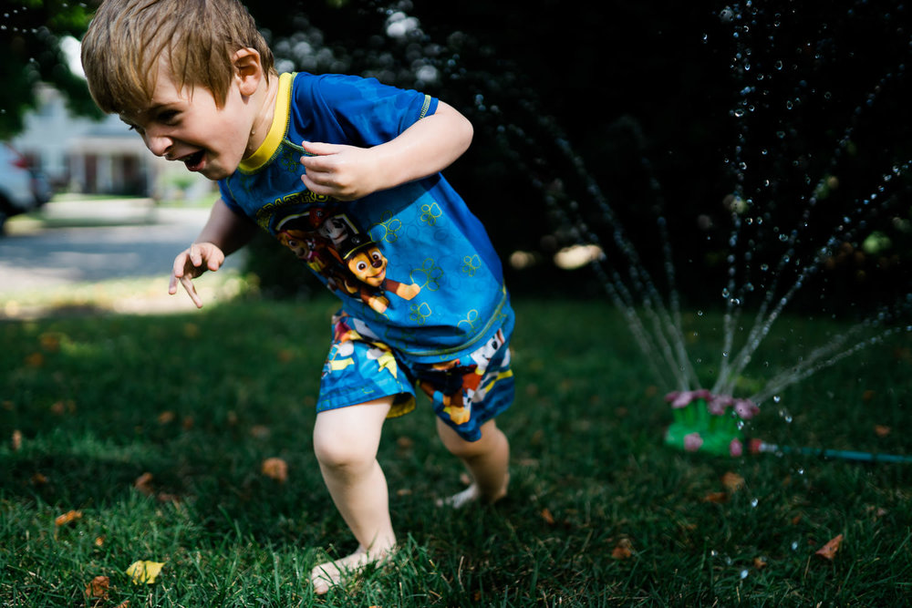 A little boy plays in the sprinkler.