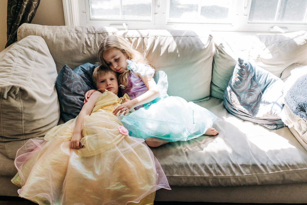 A little girl and boy dressed in princess dresses embrace on the couch.