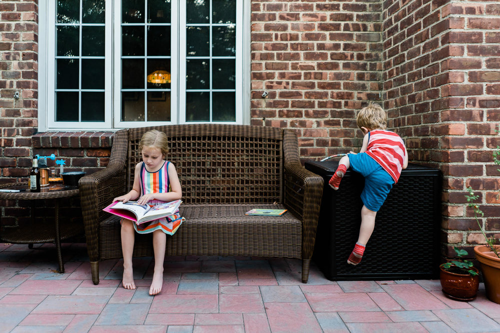 A girl and boy play on their front porch.