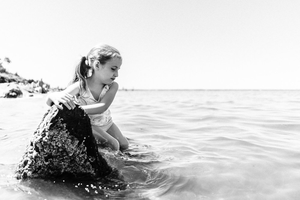 A little girl plays in the water at Sands Point.