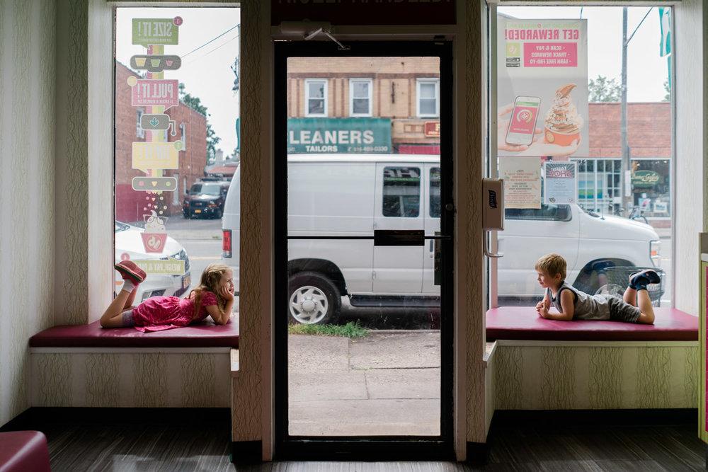 A little boy and girl sit in window seats at a frozen yogurt shop.