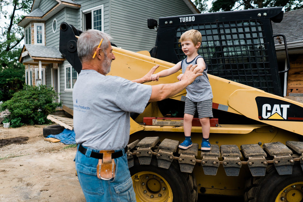 A little boy and his grandfather on a work site.